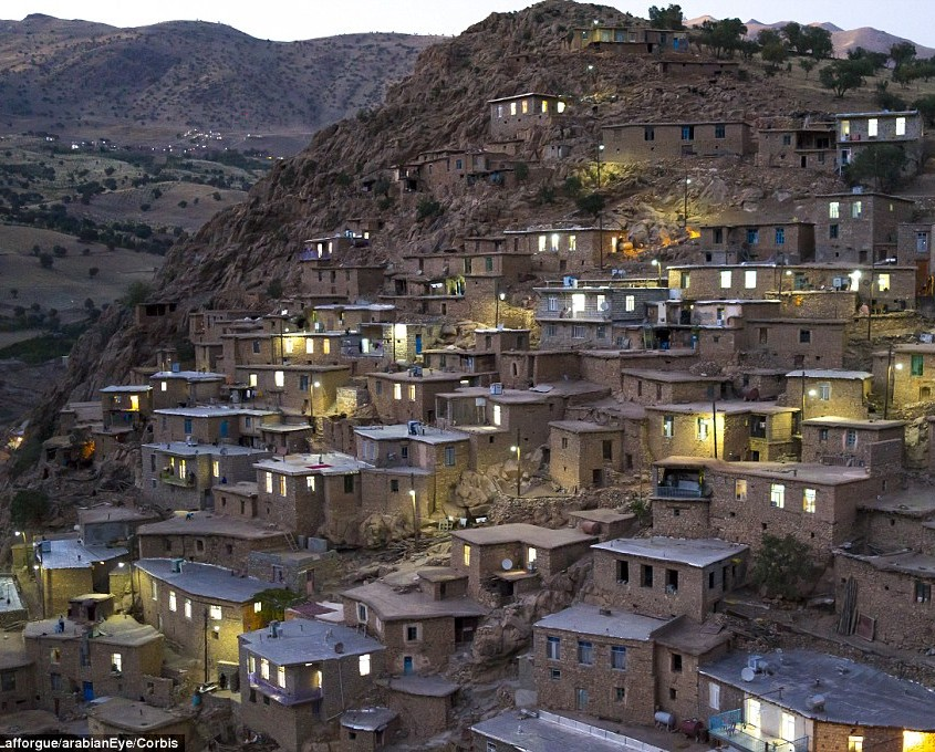 Household lights illuminate the Kurdish village of Palangan at dusk, which cascades down a steep hill